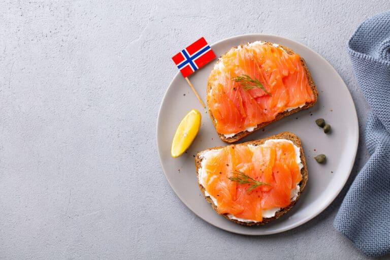 כריך, טוסט עם סלמון מעושן וגבינת שמנת בצלחת עם דגל נורווגיה.