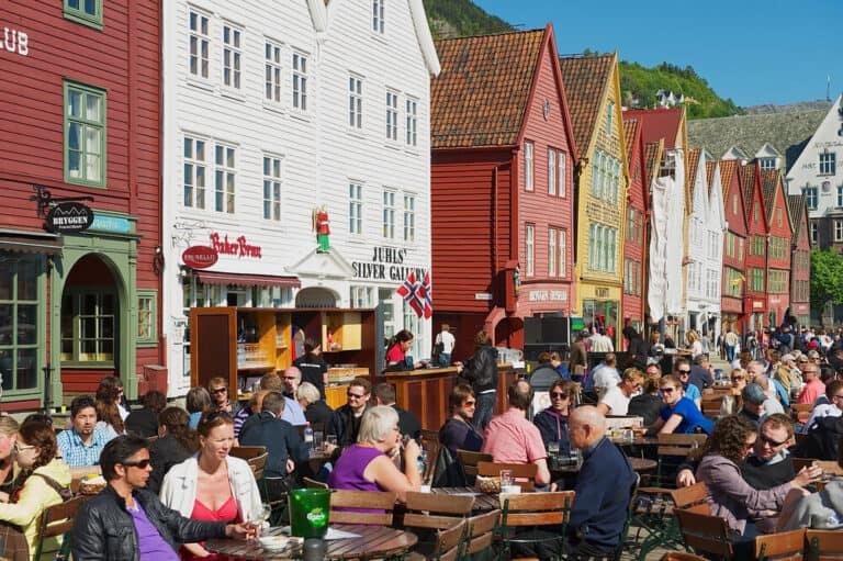 """אנשים אוכלים ארוחת צהריים במסעדות רחוב בברוגן בברגן, נורבגיה. ברוגן הוא אתר מורשת עולמית של אונסק""""ו."""