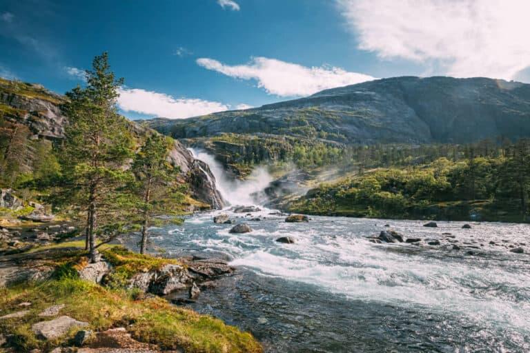 Kinsarvik, Hordaland, Norway. Waterfall Nykkjesoyfossen In Hardangervidda Mountain Plateau. Summer Sunny Day. Height Of 49 m. Famous Norwegian Landmark And Popular Destination.